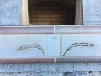 Detail of the front tiles, which we made by impressing heads of barley into clay.