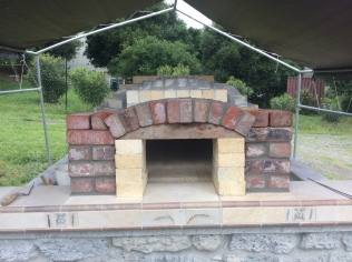Arch mortared in place, with 5th course of support columns set in place for fitting.