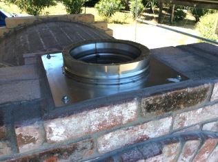 Chimney flue collar installed using thin-set mortar and expansion bolts set into brick.